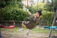 Asian child in kimono playing on swing i Stock Photo