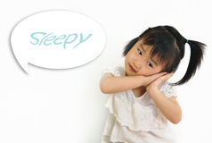 Asian child laying her head on her hands. Asian small child laying her head on her hands with sleepy word in speak bubble Stock Images