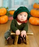 Asian child leaning on stool