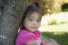 Asian child leaning on a tree Royalty Free Stock Photography