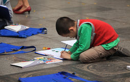 Asian child learning to draw on the ground at a park near Hoan Kiem lake in Hanoi Royalty Free Stock Photo