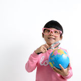 Asian child. Little Asian girl holding magnifying glass on earth globe Royalty Free Stock Image