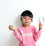 Asian child. Little Asian girl looking at the crystal globe with magnifying glass Stock Images