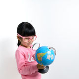 Asian child. Little Asian girl looking at the earth globe with magnifying glass Royalty Free Stock Images