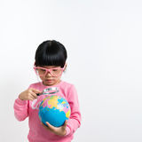 Asian child. Little Asian girl looking at the earth globe with magnifying glass Stock Photo