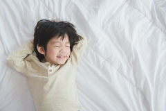 Asian child lying on white bed Stock Photography