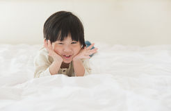 Asian child lying on white bed Royalty Free Stock Photography