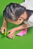 Asian child makes origami paper craft Stock Photos