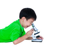 Asian child observed through a microscope biological preparation. S with copy space. Boy having education activities. Isolated on white background. Studio shot Royalty Free Stock Photo