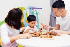 Asian child and parents playing with wooden blocks in the room at home. A kind of educational toys for preschool and kindergarten Royalty Free Stock Image