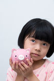Asian child with piggy bank. Asian child hold a pink piggy bank thinking Royalty Free Stock Photos