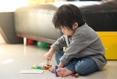 Asian child playing with colorful construction blocks Stock Photo