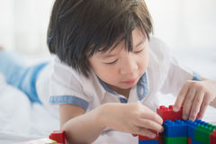 Asian child playing with colorful construction blocks Royalty Free Stock Images