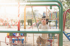 Asian child playing on playground in summer outdoor park Stock Images
