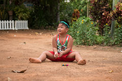 Asian child playing with sand and ball in the playground Stock Images