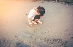 Charming young girl is looking for sea animals on the beach. Asian child playing with sand. Charming young girl is looking for sea animals on the beach. Outdoor Royalty Free Stock Images