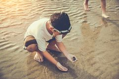 Asian child has fun digging in the sand. Young boy enjoying on b Stock Images