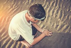 Asian child has fun digging in the sand. Young boy enjoying on b Royalty Free Stock Images