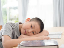 Asian child of primary school age do homework. The boy does his homework at his desk at home. The student / pupil has been bored on the lesson. Child fell Stock Photos