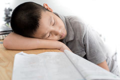 Asian child of primary school age do homework. The boy does his homework at his desk at home. The student / pupil has been bored on the lesson. Child fell Royalty Free Stock Photos