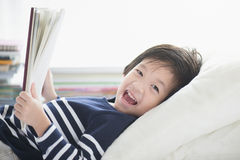 Asian child reading a book. Cute Asian child reading a book on white bed Stock Photos
