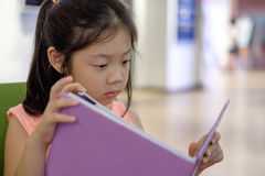 Asian Child Reading Book in Library Stock Photo
