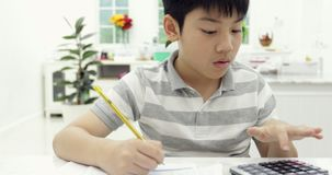Asian child reading calculating and writing to do homework at home. stock footage