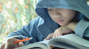 Asian child doing your homework at home. stock image
