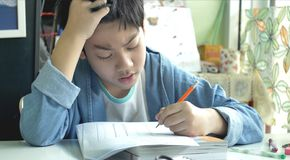 Asian child doing your homework at home. stock photo