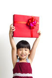 Asian child with red gift box. Asian child girl hold up high a red gift box Stock Photo