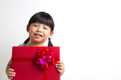 Asian child with red gift box. Portrait of Asian child girl with red gift box represents Christmas theme Royalty Free Stock Images
