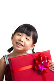 Asian child with red gift box. Portrait of Asian child girl with red gift box represents Christmas theme Stock Photo