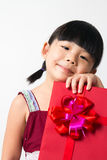 Asian child with red gift box. Portrait of Asian child girl with red gift box represents Christmas theme Stock Photos
