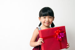 Asian child with red gift box. Portrait of Asian child girl with red gift box represents Christmas theme Royalty Free Stock Photo