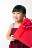 Asian child with red gift box. Portrait of Asian child girl with red gift box represents Christmas theme Royalty Free Stock Image