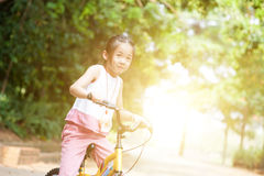 Asian child riding bicycle outdoor. Royalty Free Stock Photos