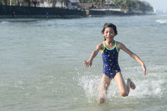 Asian child running to the sea and splashing Stock Photography