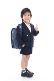 Asian child in school uniform. With blue school bag showing thumb on white background isolated Stock Photo