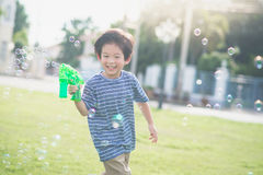 Asian child Shooting Bubbles from Bubble Gun Stock Images