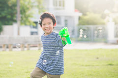 Asian child Shooting Bubbles from Bubble Gun Royalty Free Stock Photo