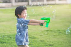 Asian child Shooting Bubbles from Bubble Gun Stock Photography