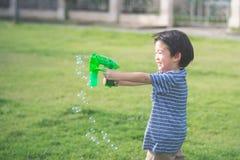 Asian child Shooting Bubbles from Bubble Gun Royalty Free Stock Photos