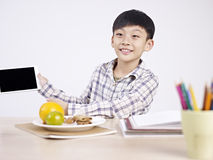 Asian child showing his tablet Royalty Free Stock Photography