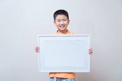 Asian child showing and holding empty white picture frame royalty free stock photo