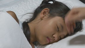 Asian child sick and sleeping on the bed