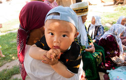 Asian child sitting on his mothers arms. KYRGYZSTAN: Child sitting on his mothers arms durring a family holiday. Kyrgyzstans population is 5.4 mill. 34% are Royalty Free Stock Image