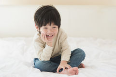 Asian child sitting on white bed Royalty Free Stock Images