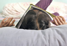 Asian child sleeping with a book covering her face royalty free stock images