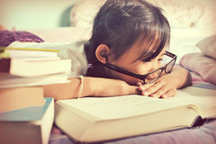 Asian child sleeping while reading in the bed. girl with glasses royalty free stock image