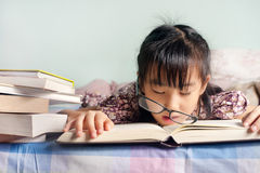 Asian child sleeping while reading in the bed. girl with glasses Royalty Free Stock Photos